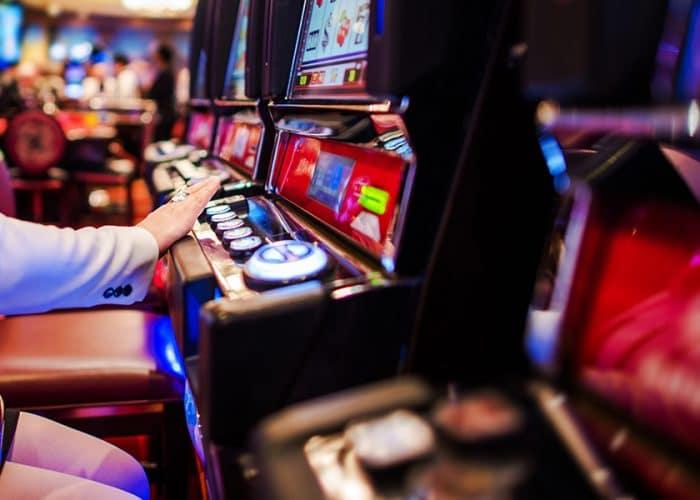 a human hand on a slot machine